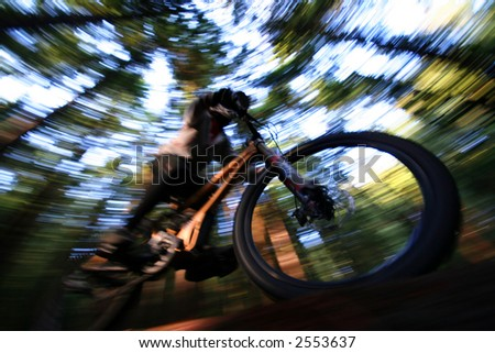 A heavily blurred mountain biker on a trail in Vancouvers famous North Shore mountains. - stock photo