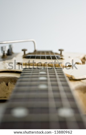 A heavily used electric guitar. Focus on 1st pickup. - stock photo