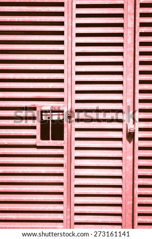A heavy duty metal gate as a background image in red monochrome - stock photo