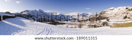 A heavy fall of snow lies on top of the mountains surrounding the Little Langdale Valley in the English Lake District. Little Langdale Tarn lies completely frozen in the foreground.  - stock photo