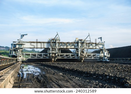 A heavy machine is called 'Reclaimer', operates in coal stock pile, Mae Moh mine, Lampang, Thailand. - stock photo