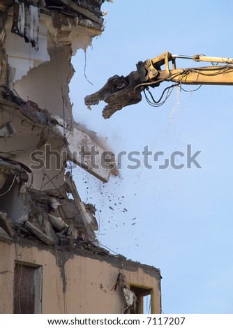 a heavy machine knocking down an old building - stock photo