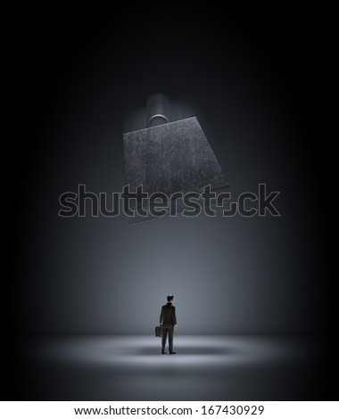 A heavy metal wieght falling on a business man - stock photo