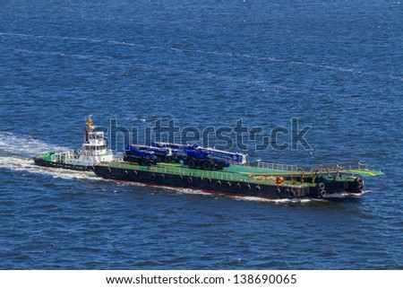 A heavy vehicle transport barge cruises across the bay.