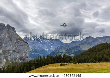 A helicopter flying over the Swiss Alps close to Wengernalp railway station