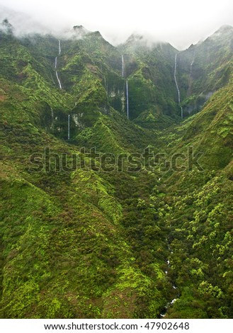 A helicopter view of waterfalls draining from the lush south side of Mount Waialeale (Wai'ale'ale), Kauai. This wilderness area is considered one of the wettest or rainiest spot on earth. - stock photo