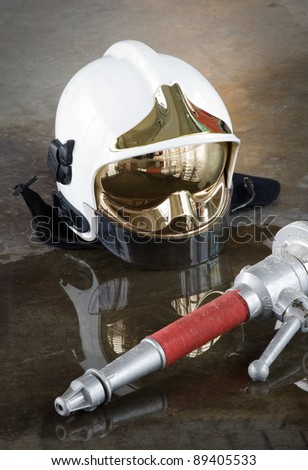 A helmet and a nozzle on the floor in a fire station used by firefighters - stock photo