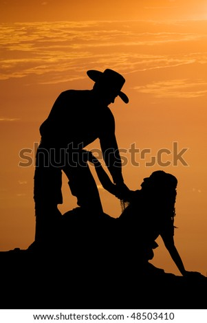A hero of a cowboy helping up his girl after falling, with a beautiful orange sunset behind them. - stock photo