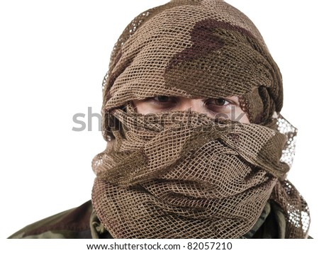 A hidden face of a guerrilla warrior with serious stare on his eyes. - stock photo