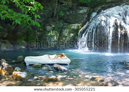 A hidden place. Sleeping woman in deep forest lies on airbed. Waterfall on back - stock photo