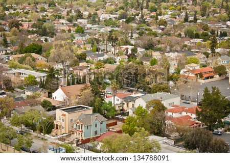 A high angle view of a typical housing area in an urban area with a variety of residential buildings, including two Victorian style houses in the foreground. San Jose, California. - stock photo
