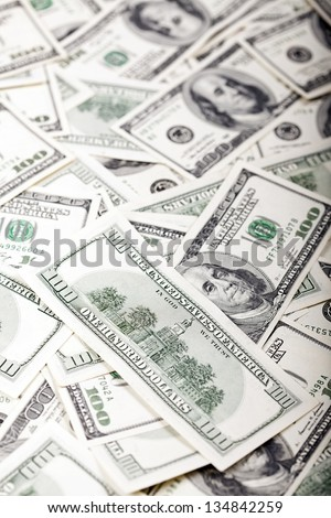 A high angle view of a very large amount of 100 US$ money notes in a bulky mess. On the front there is a note showing its reverse side, depicting the Independence Hall. - stock photo