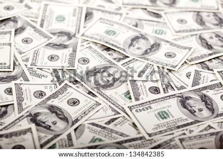 A high angle view of a very large amount of 100 US$ money notes in a bulky mess. Shallow depth of field. - stock photo