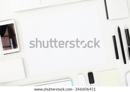 A high angle view of blank paper surounded by various office items - stock photo