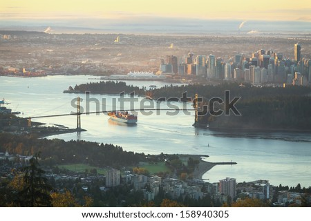 A high angle view of downtown Vancouver, the Lions Gate Bridge, and Burrard Inlet at sunrise. A freighter passes under the bridge as the sun comes up. British Columbia, Canada. - stock photo