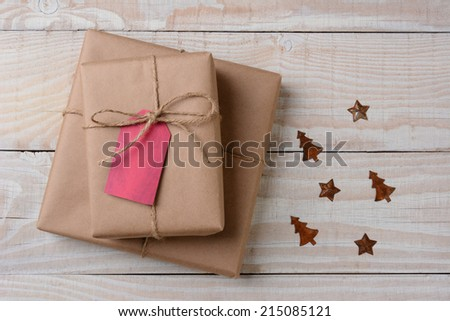 A high angle view of plain brown paper wrapped presents with red tags on a white rustic table. Small rusty metal ornaments in star and tree shapes lay by their side. Horizontal format. - stock photo