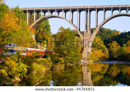 A high arched bridge spans a river and passenger train - stock photo