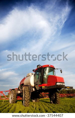 A high clearance spayer with nice clouds - stock photo