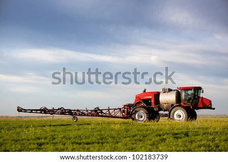 A high clearance sprayer on a field  in a prairie landscape - stock photo