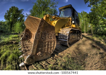 A High Dynamic Range wide angle photo of a bulldozer at a construction site.