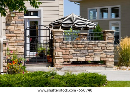A high end patio home or townhome entrance with striking black and white patio umbrella. - stock photo