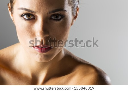 A high fashion brunette model posing in a studio environment. - stock photo