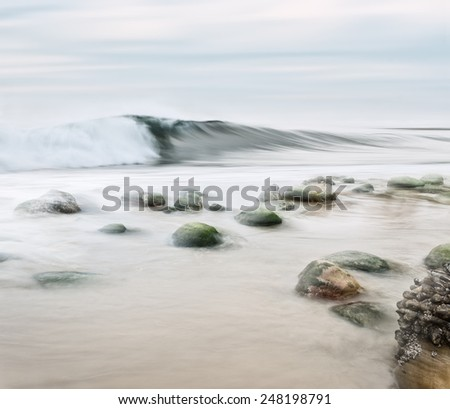A high key seascape with desaturated colors.  Image made with panning motion for a semi-blurred effect. - stock photo