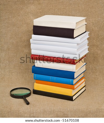 A high pile of books and magnifying glass - Educational still life - stock photo