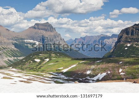 A high plateau in summer with snow melting into green fields surrounded by enormous mountains of Glacier National Park, Montana. - stock photo