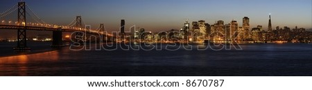 A high-resolution stitched image of Bay Bridge and San Francisco downtown decorated by Christmas lighting at dusk (shot from Treasure Island). Copyspace on top and bottom. - stock photo