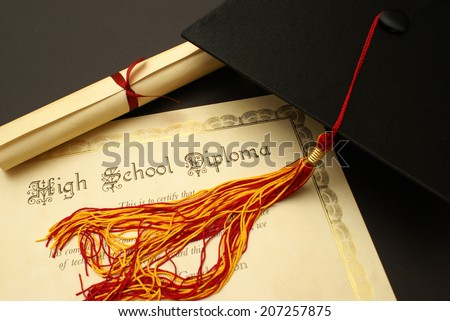 A high school diploma and mortarboard for this students achievements. - stock photo