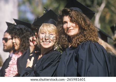 A high school graduate pins a buttoneer on her boyfriend, Providence, RI - stock photo