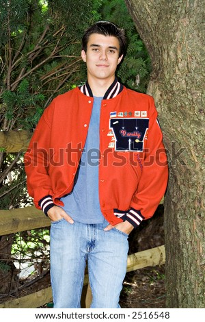 A high-school senior in his school varsity letter jacket. - stock photo