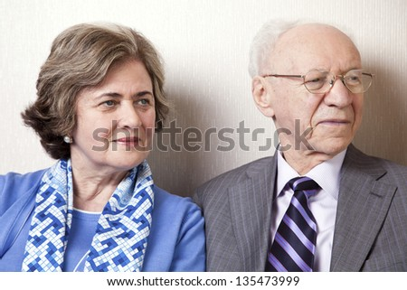 A high society senior couple (he's in his 80's, she's in her late 60's) sitting on a sofa looking away to the right side of the frame. - stock photo