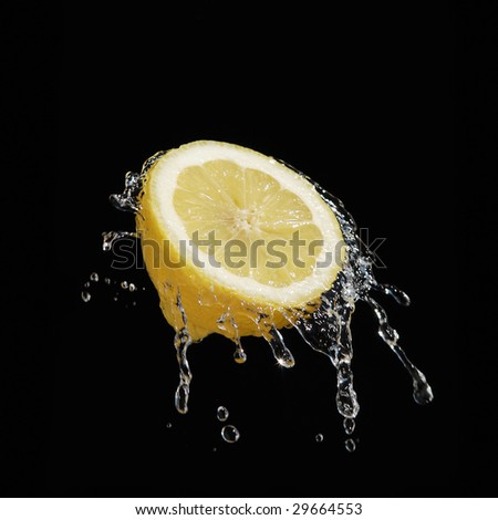 A high-speed shot of a lemon with splashing water, isolated on a black background. - stock photo