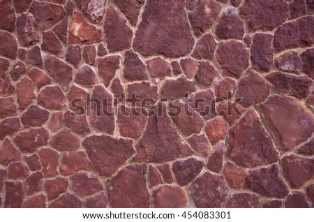 A high stone wall, lined with sandstone slabs of red color. Pattern formed by sandstone rocks of various shapes. Sandstone texture background. Wall, built of natural stone - stock photo