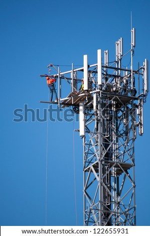 A high telecommunications tower receives some maintenance work on a cloudless day