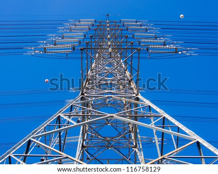 a high-voltage electricity pylons against blue sky - stock photo
