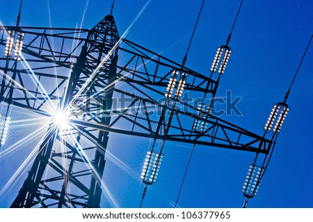 a high-voltage electricity pylons against blue sky and sun rays - stock photo
