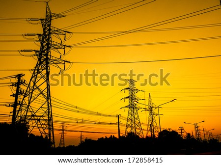 A high voltage post on yellow background - stock photo