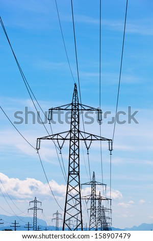 a high voltage power pylons against blue sky.