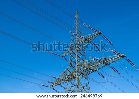 a high voltage power pylons against blue sky - stock photo