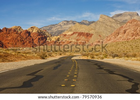 A highway curving through the desert into distant mountains - stock photo