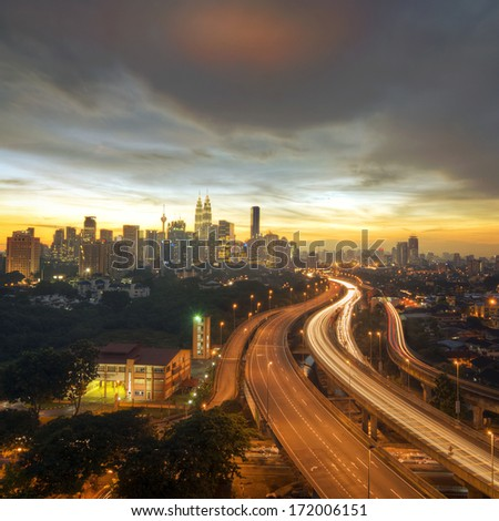 a highway lead to kuala lumpur city during sunset - stock photo