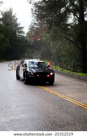 A highway patrol vehicle in pursuit of a fleeing felon on a rainy highway