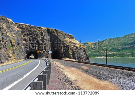 A highway running along a set of train tracks that runs along the river bank both lead to the sheer rock face natural tunnel portals as you can see the light on the other side of the tunnel. - stock photo