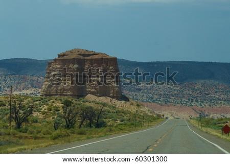 A highway running beside a mesa. - stock photo