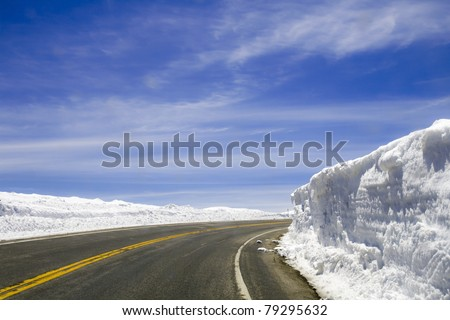 A highway that disappears around a corner is surrounded by snow walls that have been cut by a plow on a sunny day - stock photo