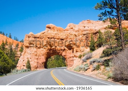 A highway tunnels through the red rock of Utah - stock photo