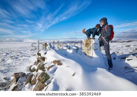 A hiker and their dog atthe summit of Geal-charn Mor, Cairngorms in the Scottish Highlands, UK. - stock photo